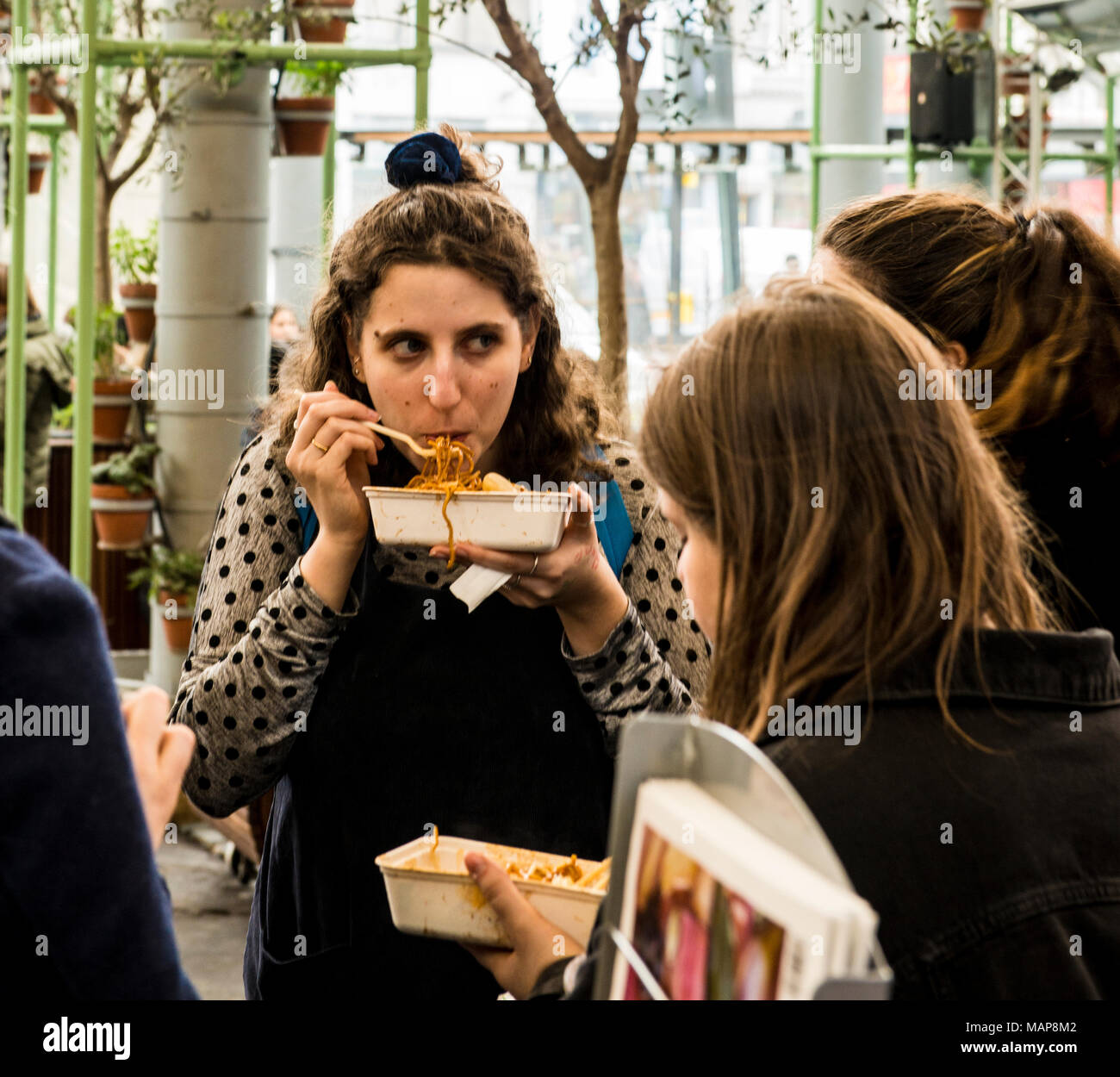 Woman eating noodles from container, Borough Market, Southwark, London, England, UK - Stock Image