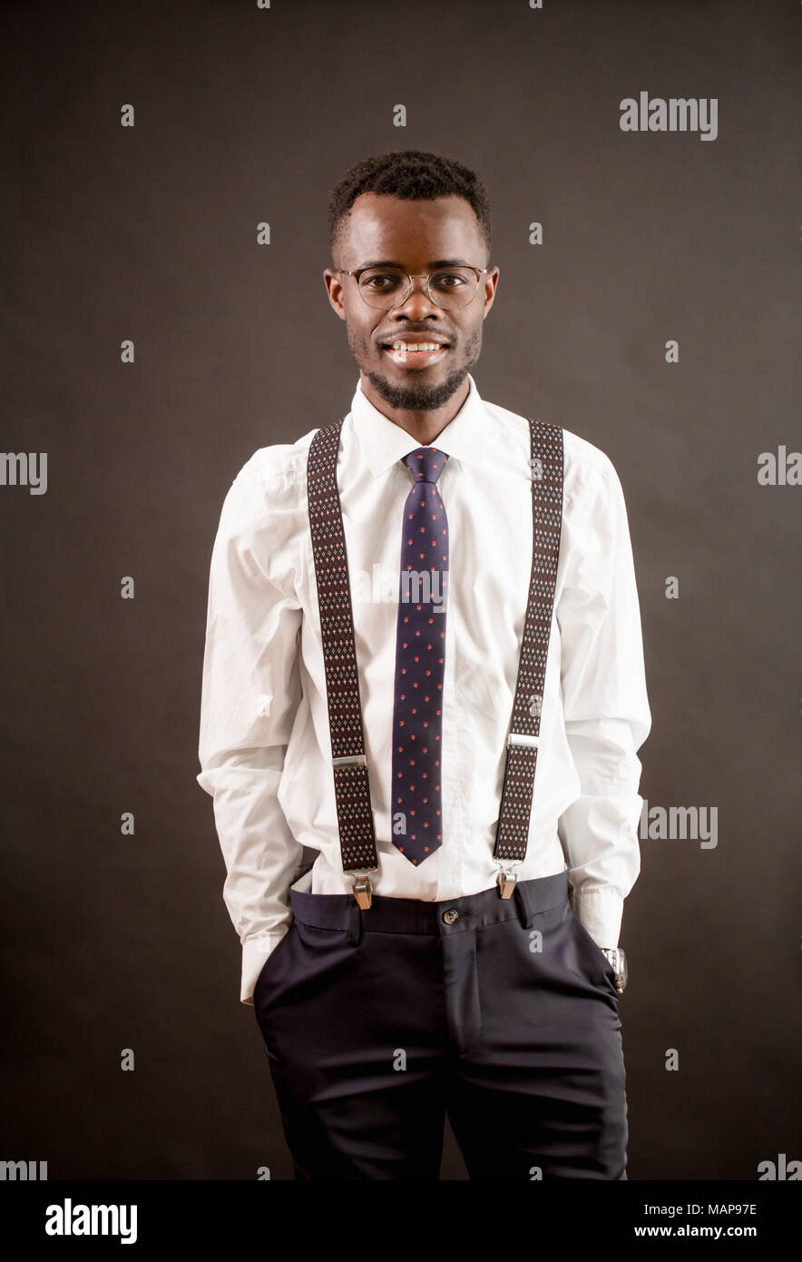 trendy African man with glasses, suspenders, white shirt, trousers and tie - Stock Image