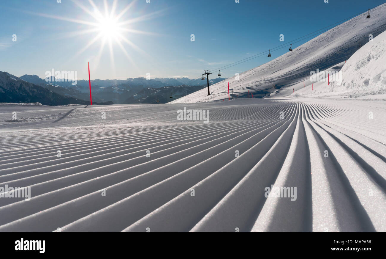 panorama view of a ski resort with freshly groomed ski slopes and ski lifts on a gorgeous winter day with a fantastic view of the surroundings - Stock Image
