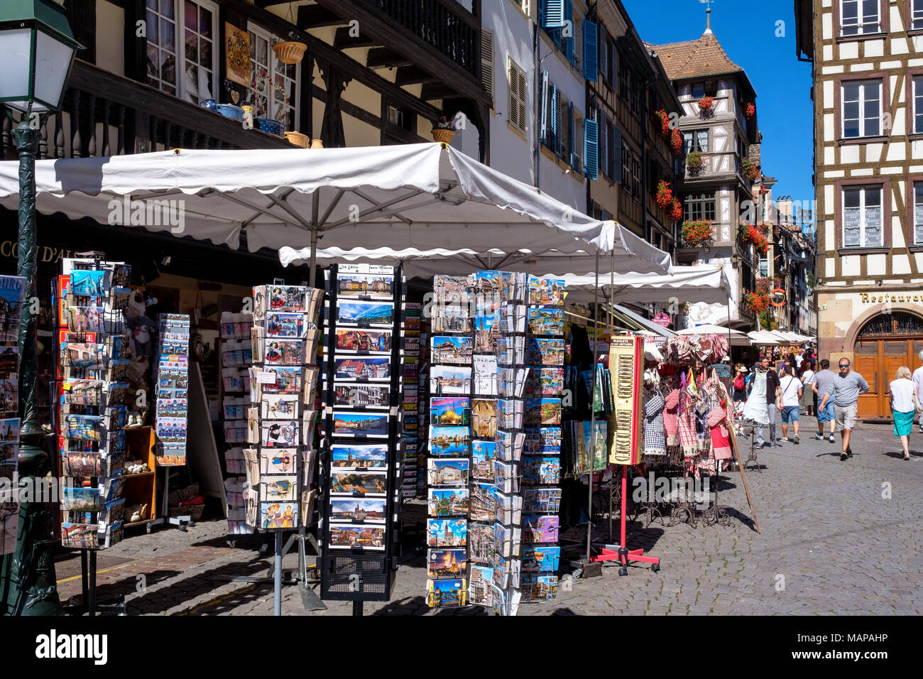 Postcards for sale on display stands, people, place du Marché aux Cochons de Lait square, Strasbourg, Alsace, France, Europe, - Stock Image
