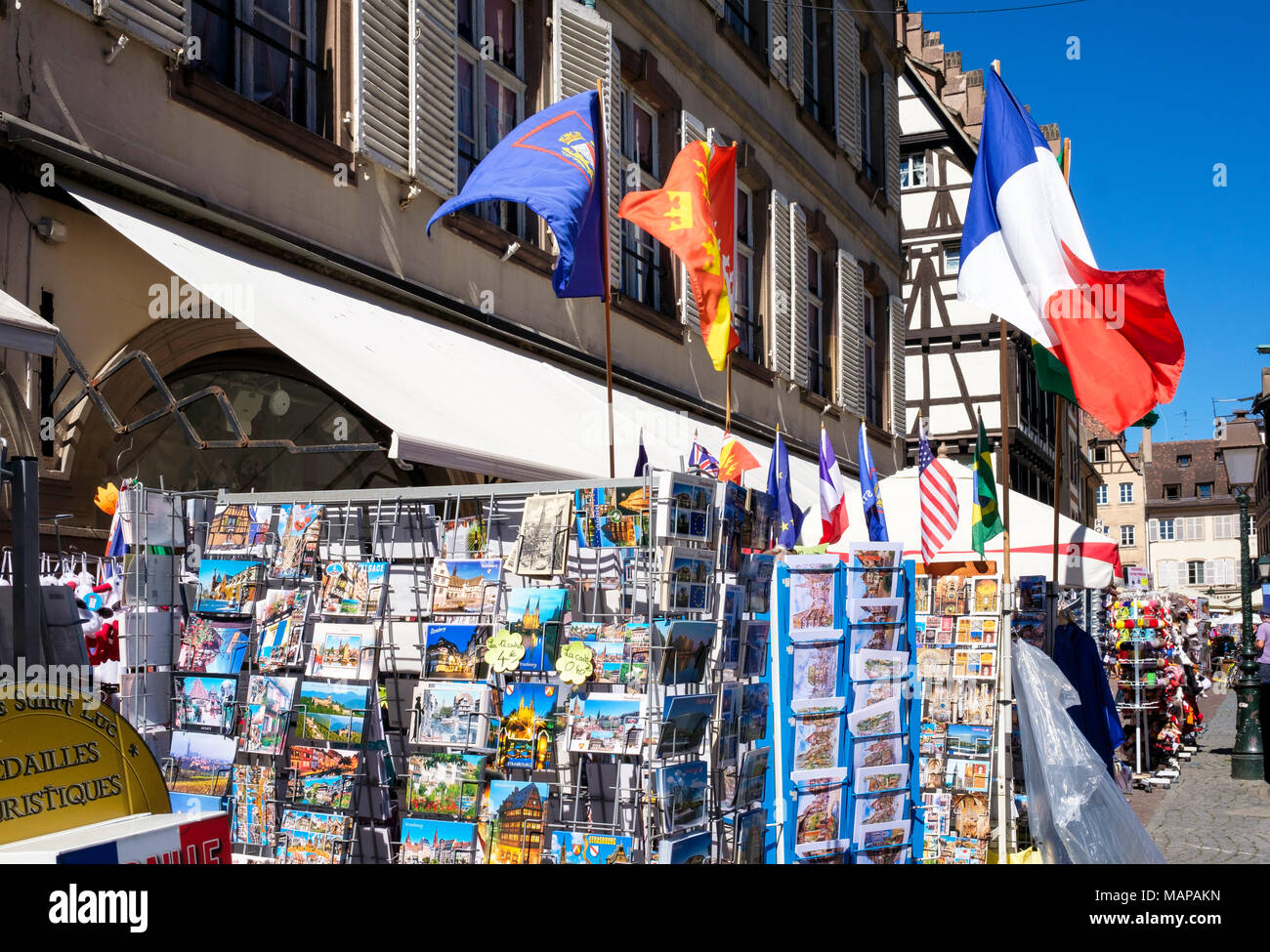 Postcards for sale on display stands, flying French flag, place de la Cathédrale, cathedral square, Strasbourg, Alsace, France, Europe, - Stock Image