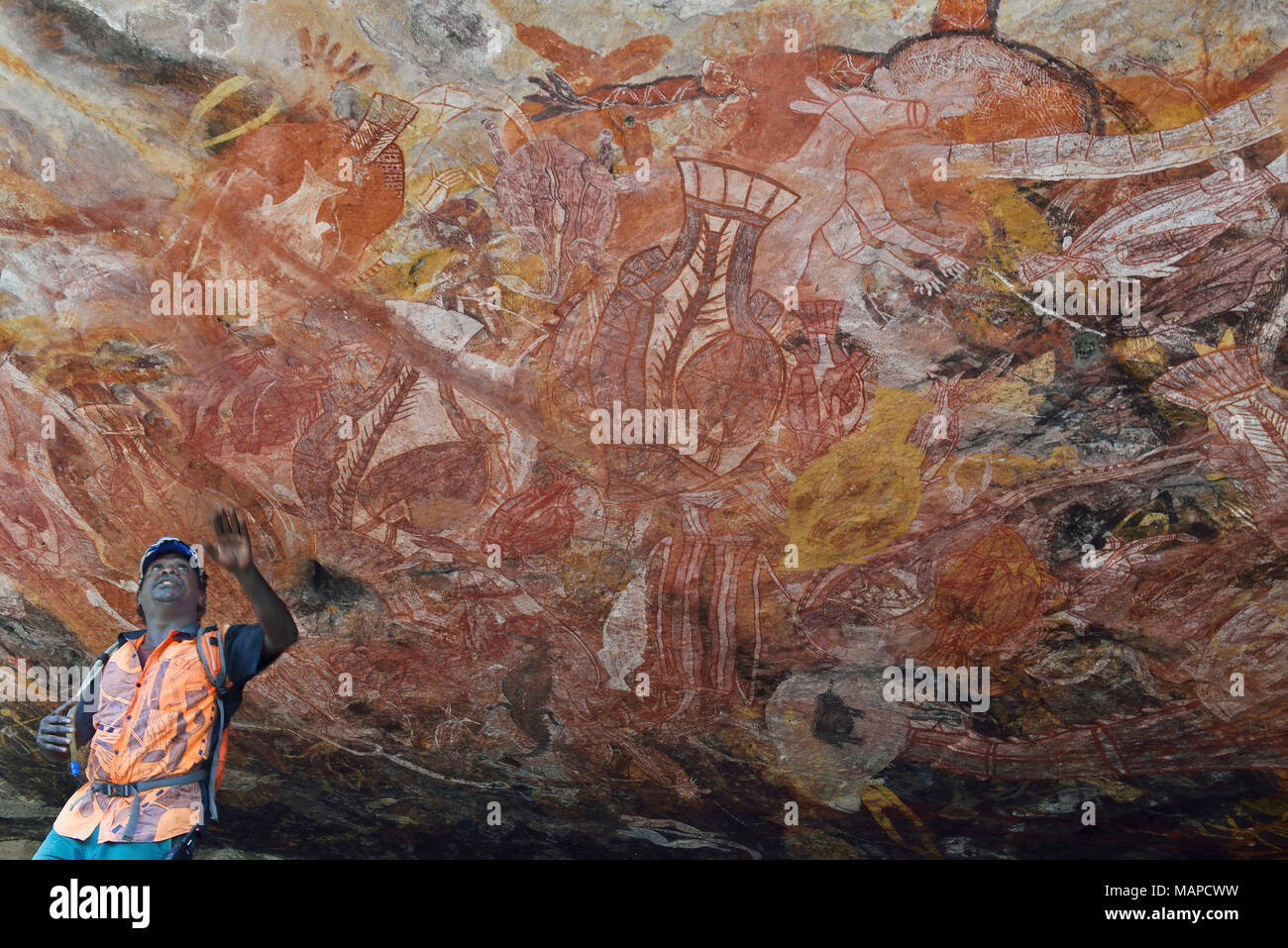 Roland, an  aboriginal  guide  local from the Gunbalanya community shows  the extensive  Rock Art  in the  towering escarpment Injalak Hill. - Stock Image