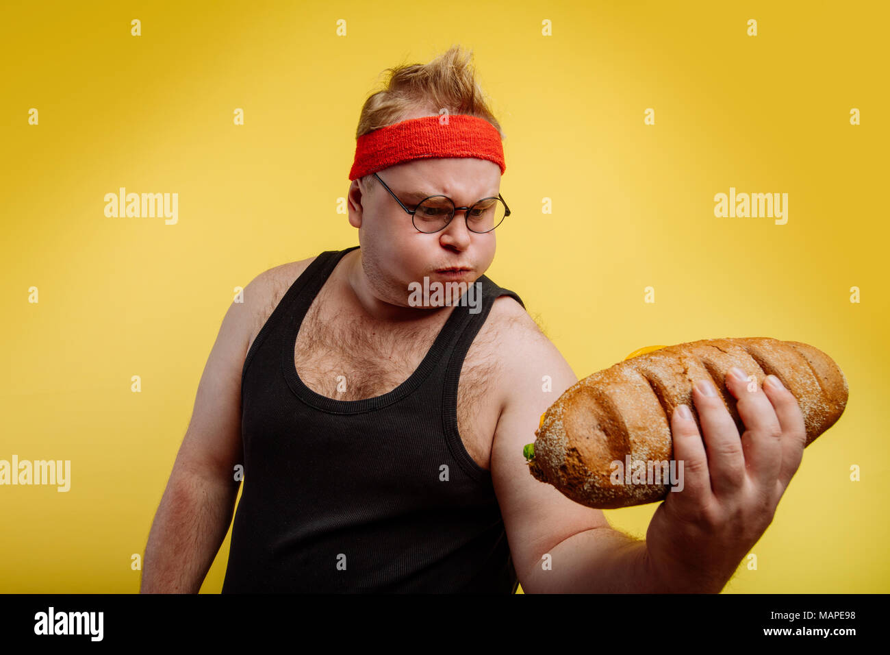 funny fat man sweats while lifting burger - Stock Image