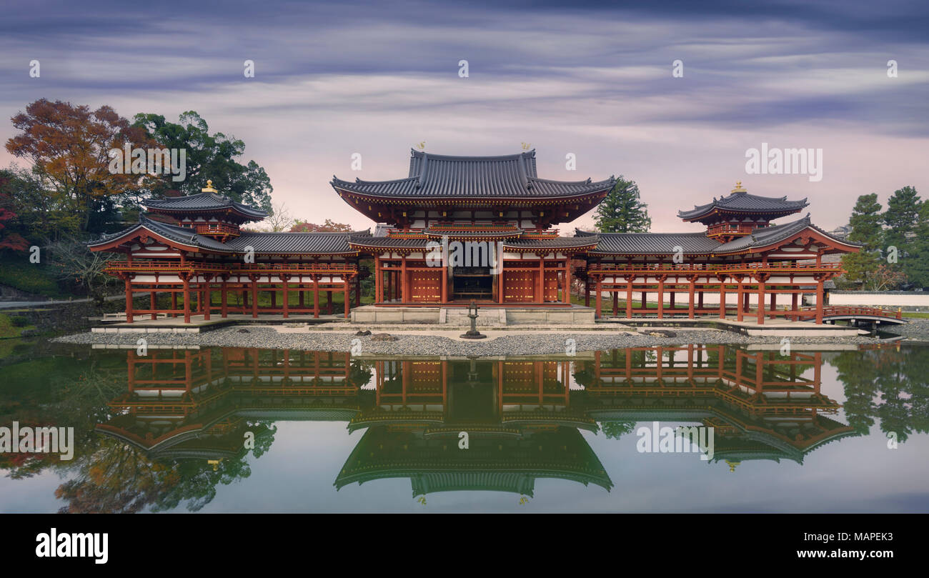 Beautiful Amida Hall of Byodoin Japanese Buddhist temple reflecting in the water of Jodoshiki Pure Land garden pond in a peaceful autumn morning scene Stock Photo