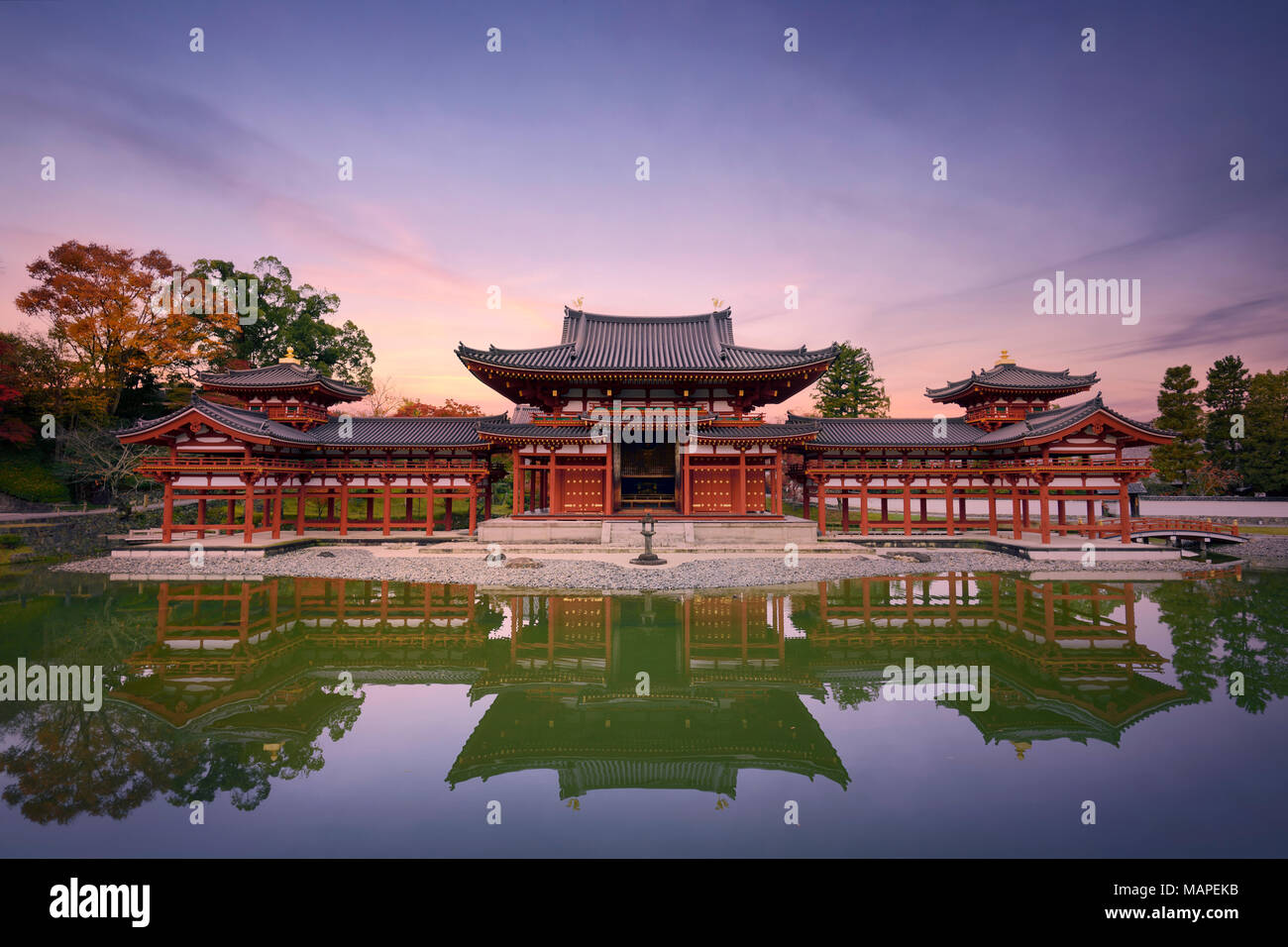 Beautiful tranquil sunset scenery of the Phoenix or Amida Hall of Byodoin, Byodo-in Japanese Buddhist temple reflecting in the clear calm water of Jod - Stock Image