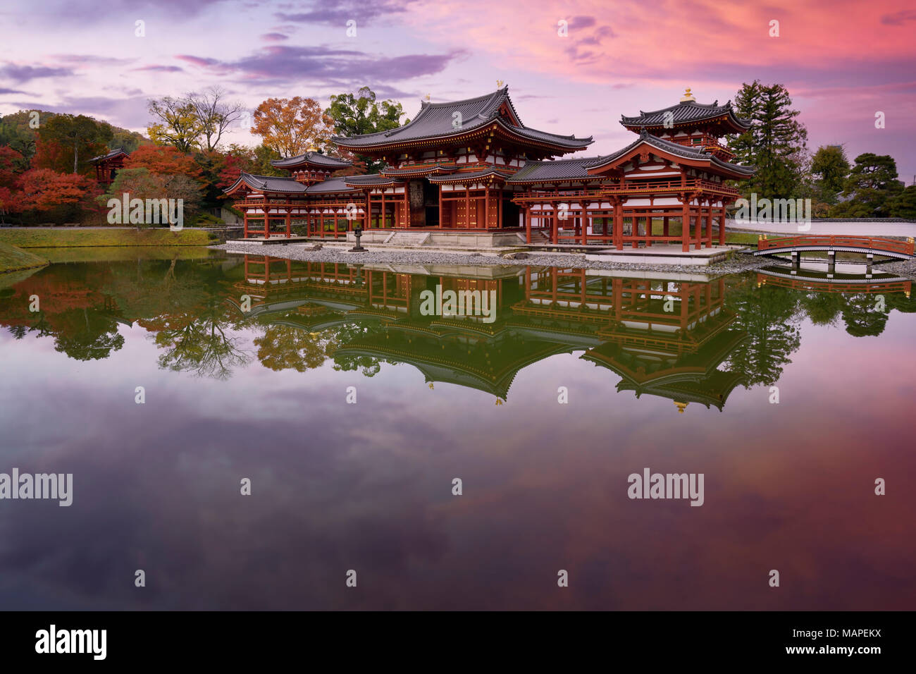 Peaceful autumn scenery of the Phoenix Hall, Amida hall of Byodoin temple on Kojima island of Jodoshiki teien, Pure Land garden pond. Uji, Kyoto Prefe - Stock Image