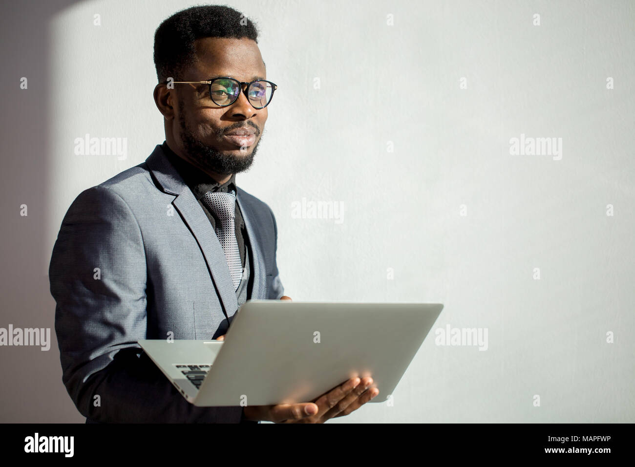 african coworker wearing glasses and using laptop in office - Stock Image