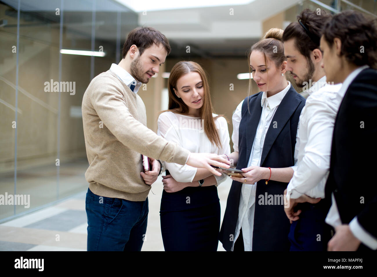 businesspeople using digital tablet together in office - Stock Image