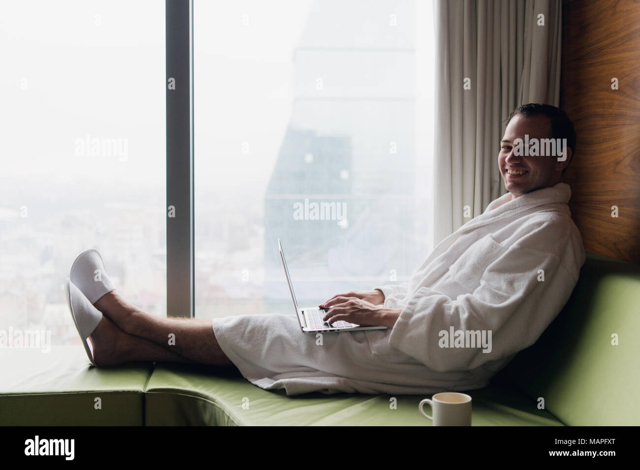 Young smiling businessman working on laptop computer wearing white bath robe sitting near window with cup of coffee looking at sunrise city view. Motivation concept - Stock Image