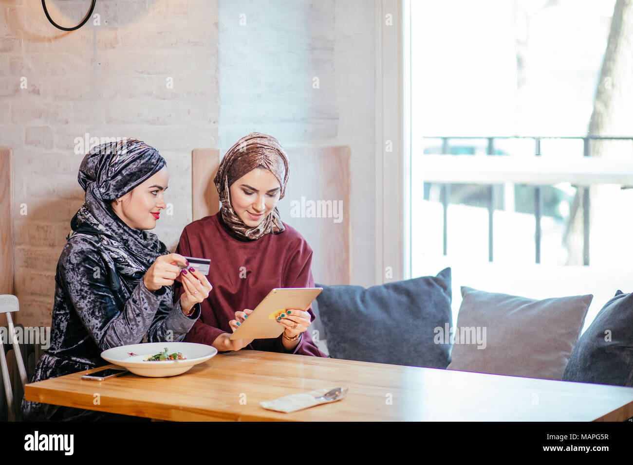 Two Muslim women in cafe, shop online using electronic tablet - Stock Image