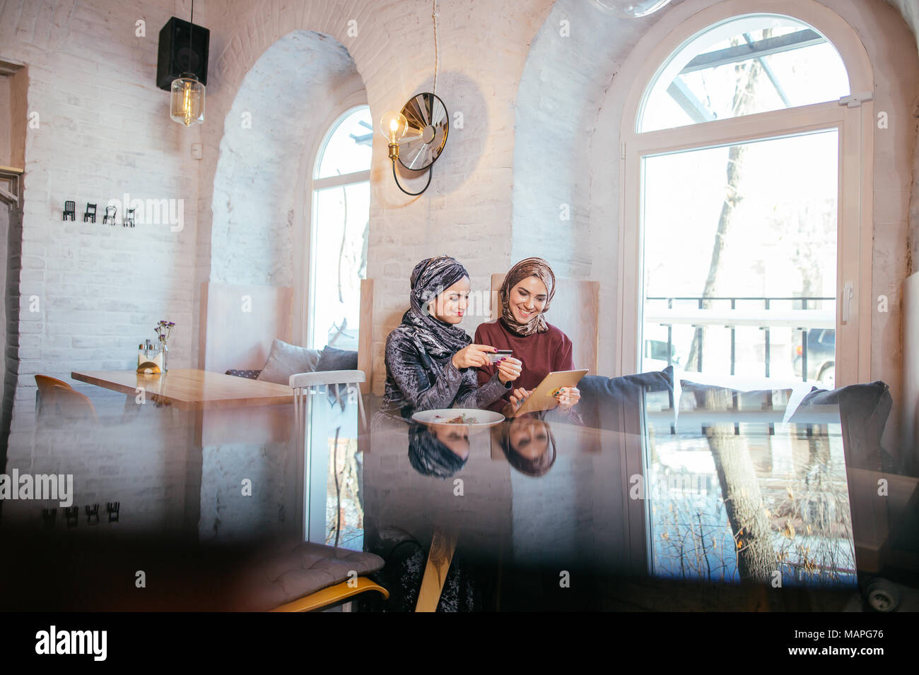 two business partner using tablet in front of their coffee shop - Stock Image
