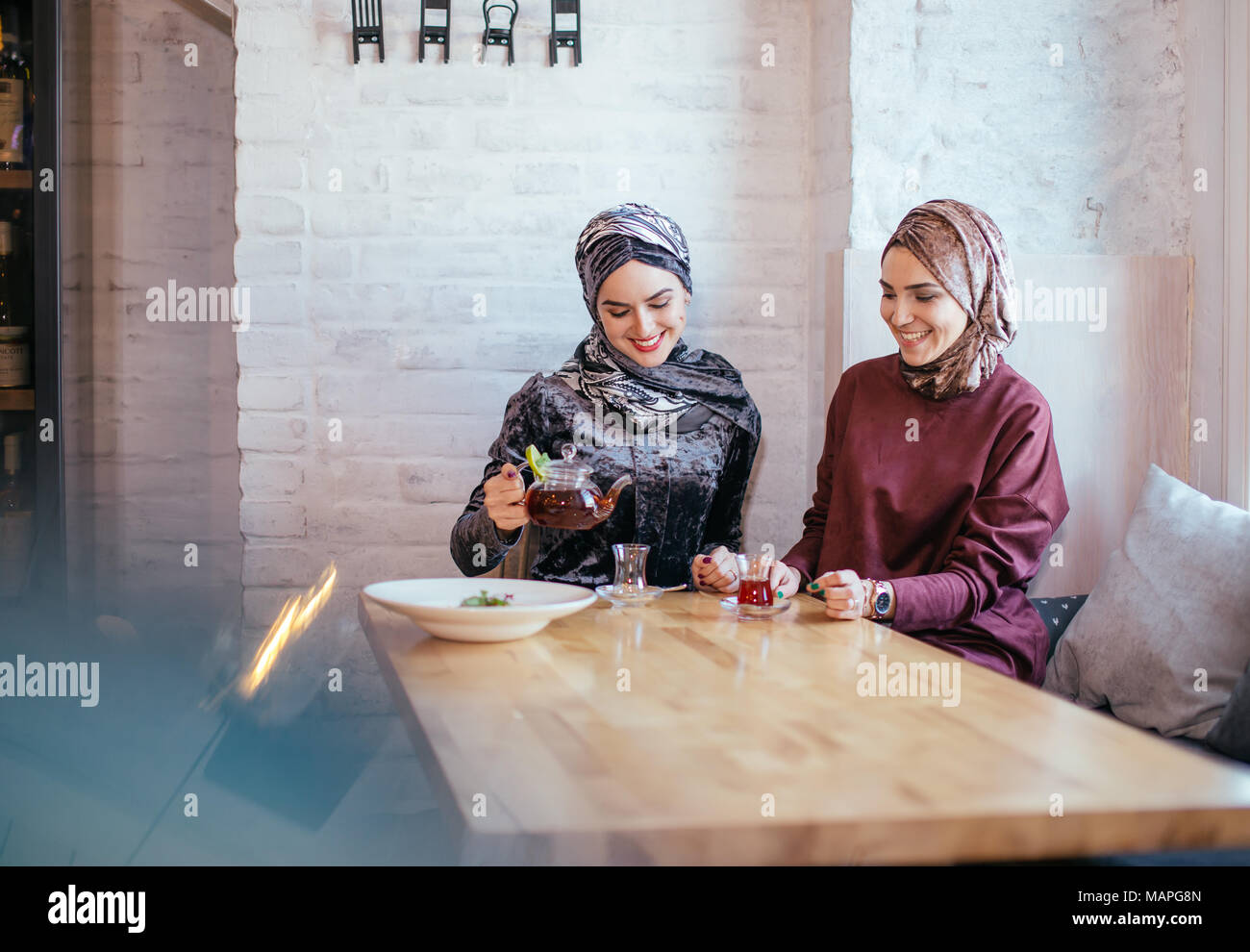 two caucasian muslim woman drinking tea in cafe - Stock Image
