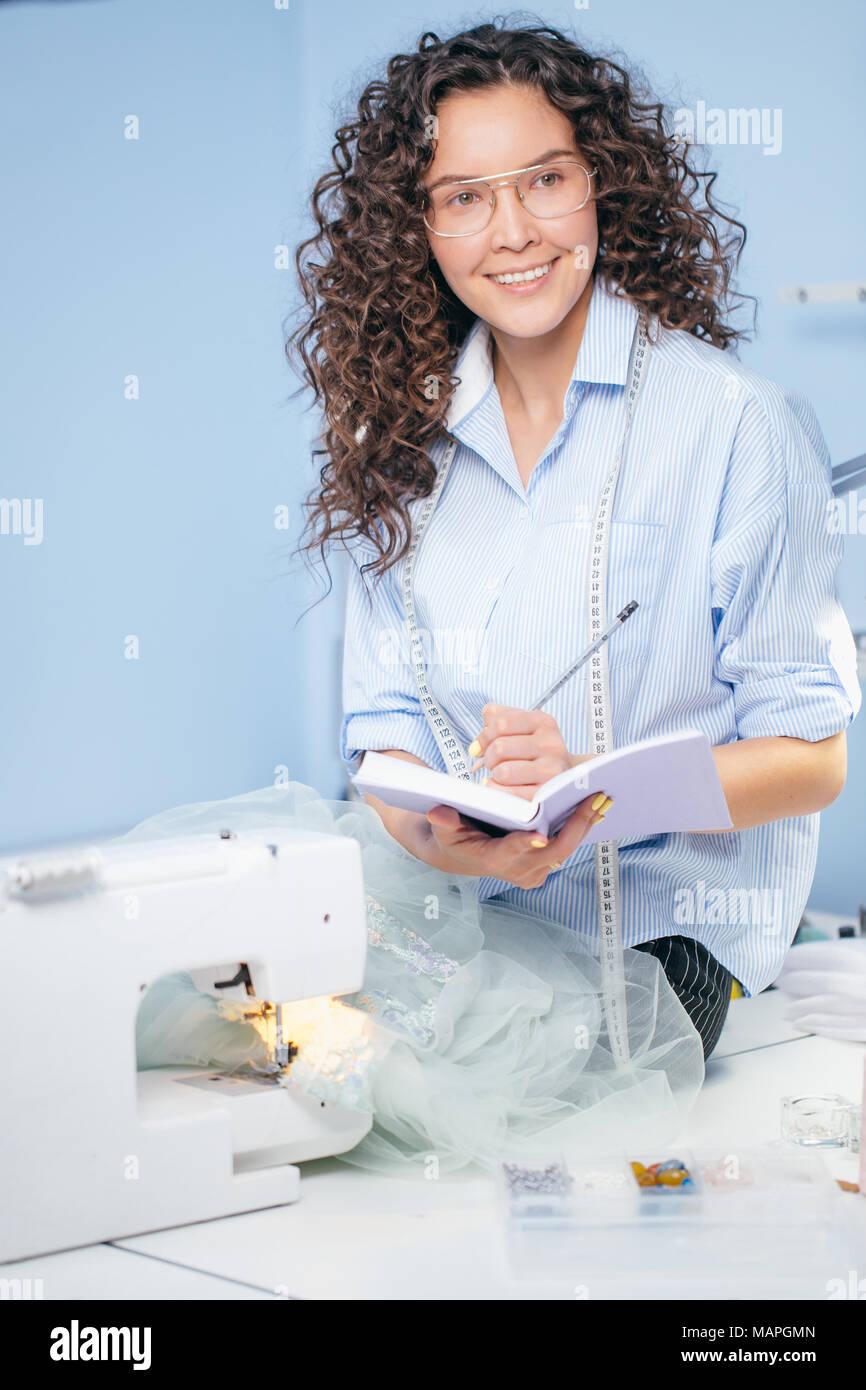 dressmaker making up design of garment - Stock Image