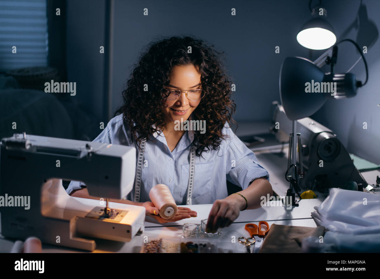 dressmaker is threading beads in front of stitching machine in black room - Stock Image