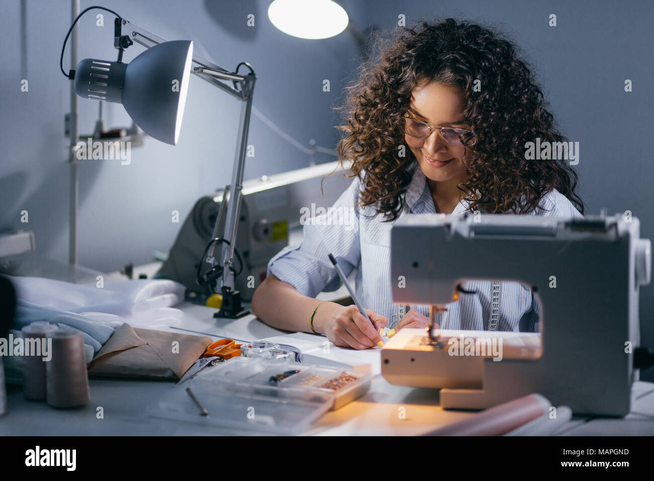 female is drawing up a draft in front of sewing machine - Stock Image