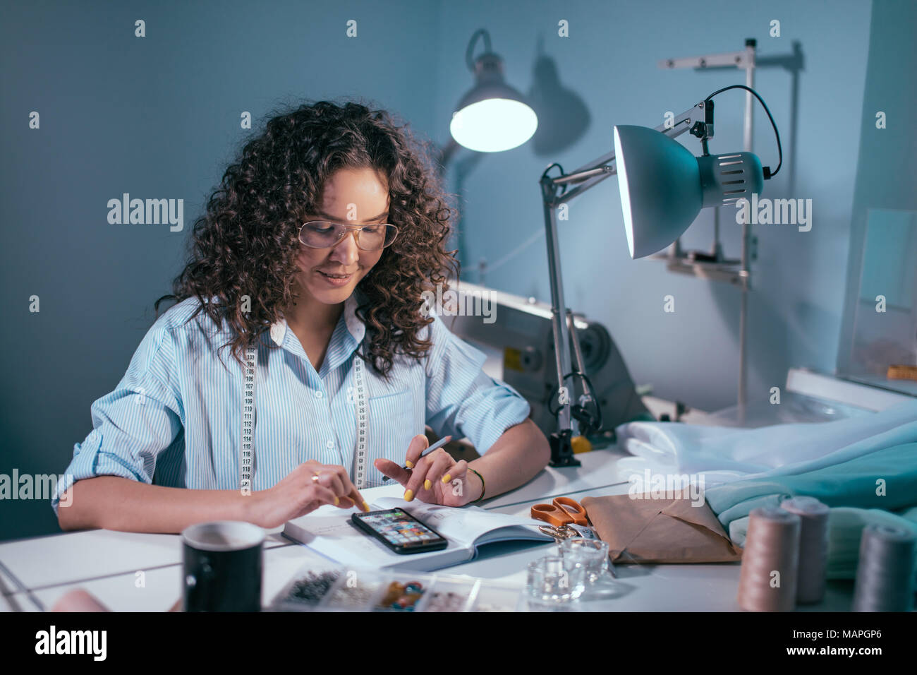 female tailor choosing models for sewng from the cellphone - Stock Image