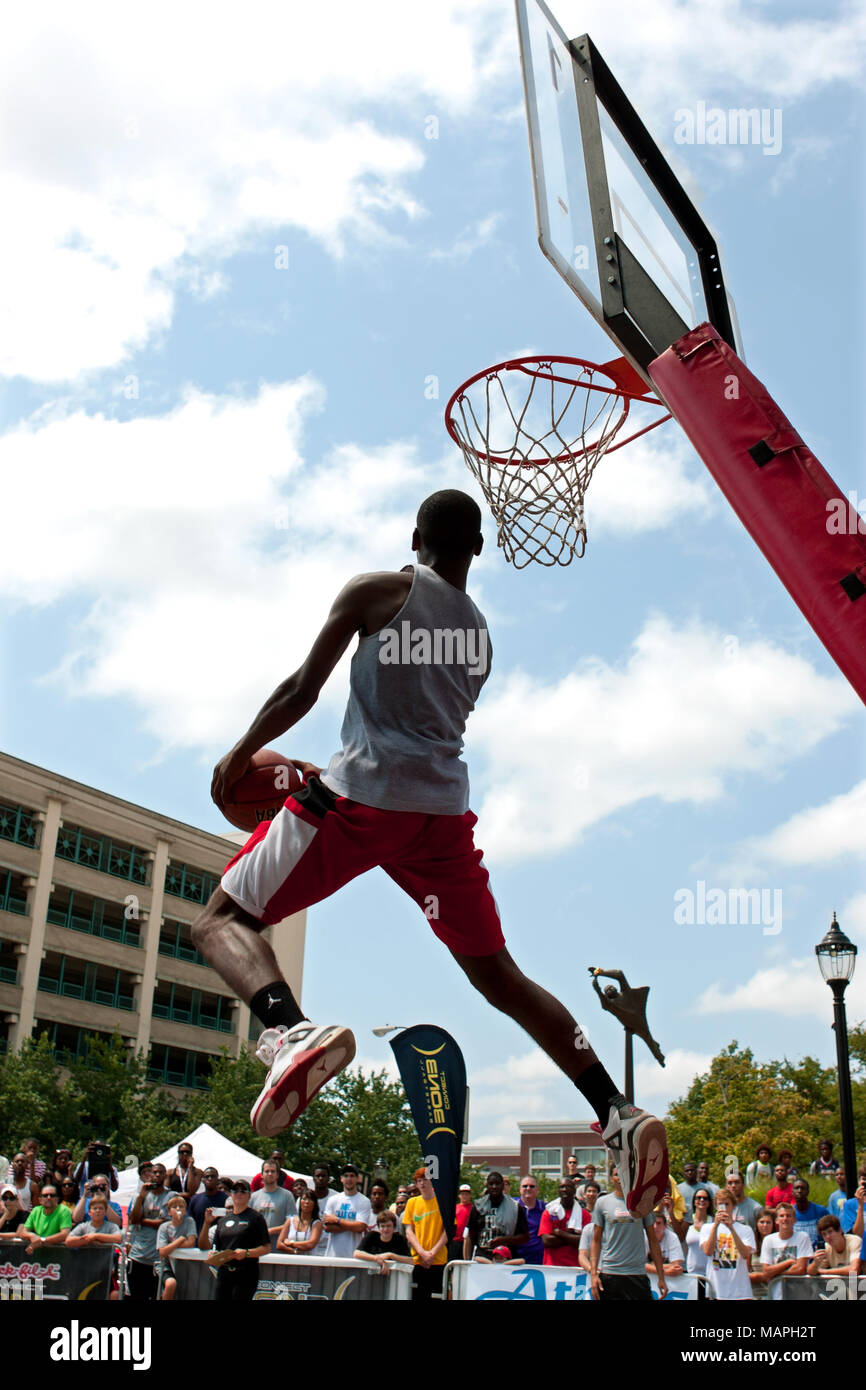 A young man jumps high attempting a reverse dunk in the slam dunk competition of a 3-on-3 basketball tournament in Athens, GA, on August 24, 2013. - Stock Image