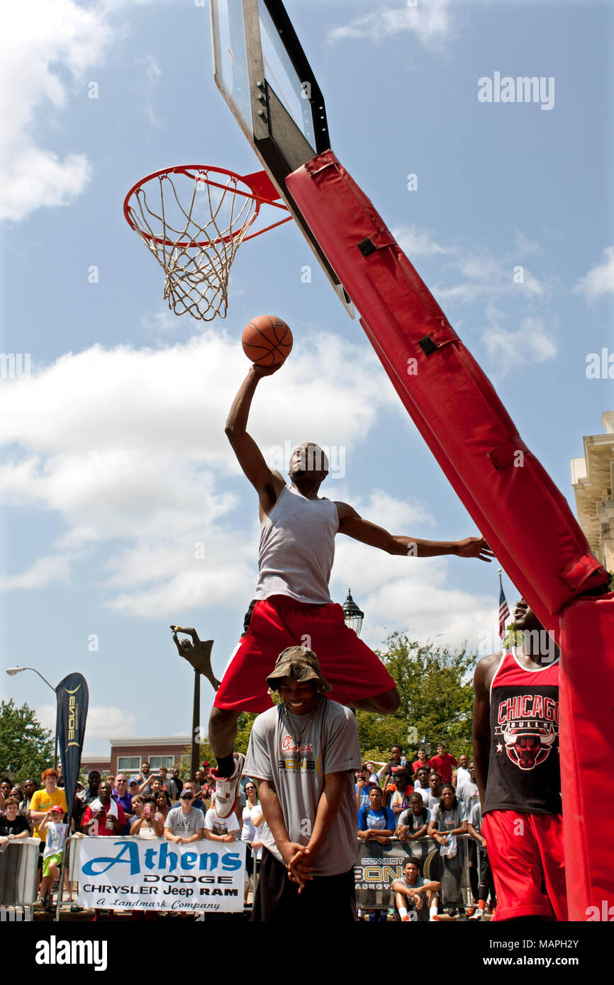 A young man jumps over someone to dunk a basketball in the slam dunk competition of a 3-on-3 basketball tournament in Athens, GA,  on August 24, 2013. - Stock Image