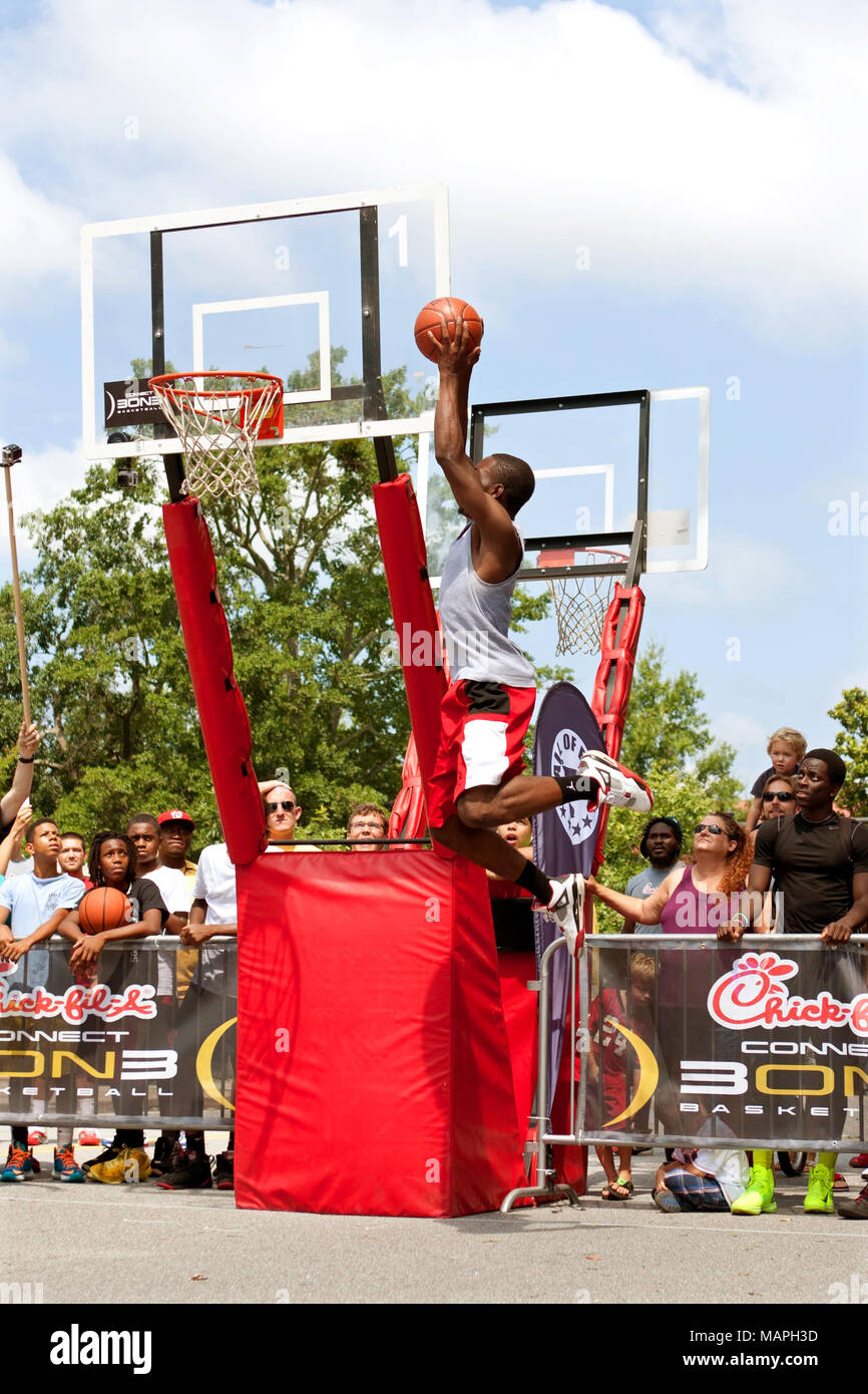 A young man jumps above the rim to dunk a basketball in the slam dunk competition of a 3-on-3 basketball tournament in Athens, GA on August 24, 2013. - Stock Image