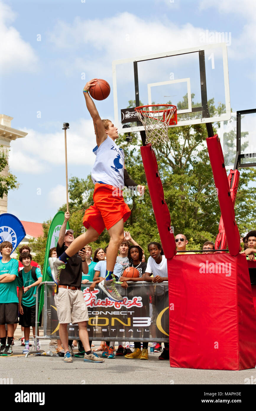 A young man soars above the rim to dunk a basketball in the slam dunk competition of a 3-on-3 basketball tournament in Athens, GA on August 24, 2013. - Stock Image