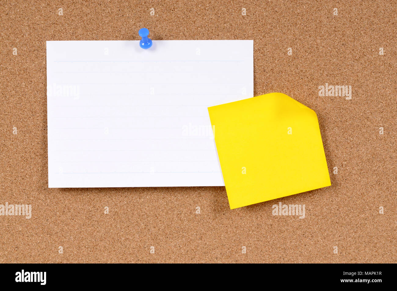Office index card and sticky note pinned to a cork bulletin
