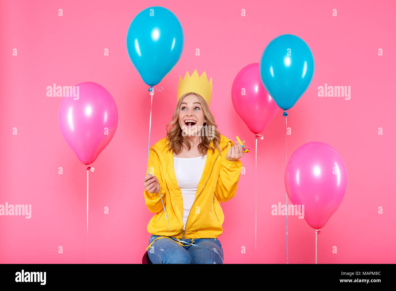 Funny girl in birthday hat, balloons and blowout horn on pastel pink background. Attractive trendy teenager celebrating birthday. - Stock Image