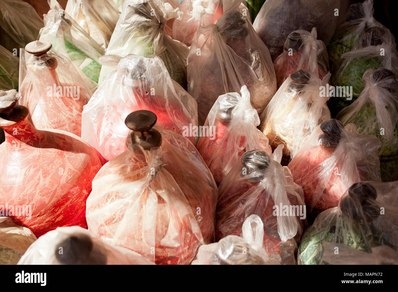 Un-necessary plastic wrapped around bottles in the souk in the centre of Nizwa, Oman - Stock Image