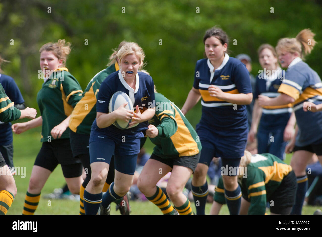 girl running with ball in rugby game - Stock Image