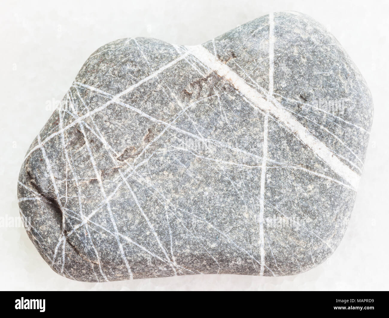 macro shooting of natural mineral rock specimen - Greywacke sandstone on white marble background Stock Photo