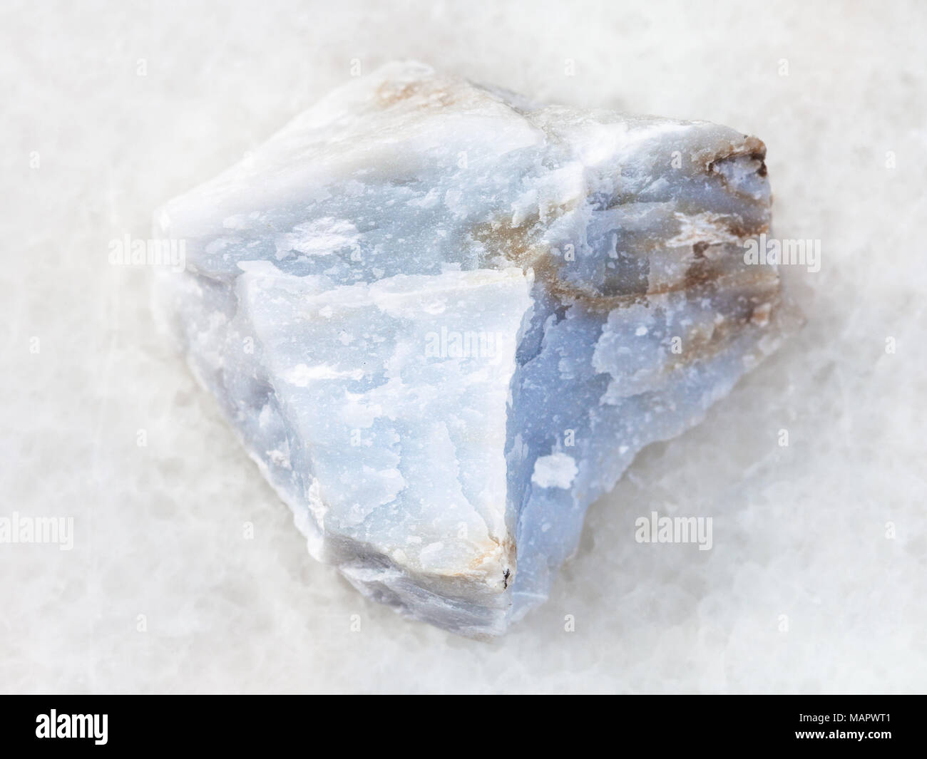 macro shooting of natural mineral rock specimen - raw Angelite (Blue Anhydrite) stone on white marble background from North Caucasian region, Russia - Stock Image