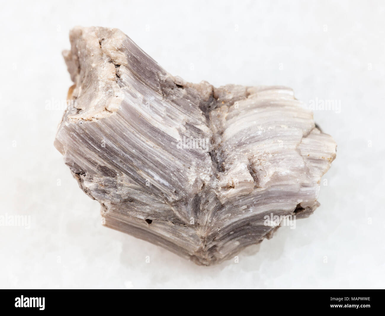macro shooting of natural mineral rock specimen - rough baryte stone on white marble background from Irkutsk region, Russia - Stock Image