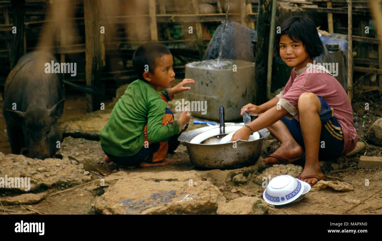 Young indigenous Akha hilltribe children washing dishes in a pig pen (pig sty) in their village in northern Thailand. - Stock Image
