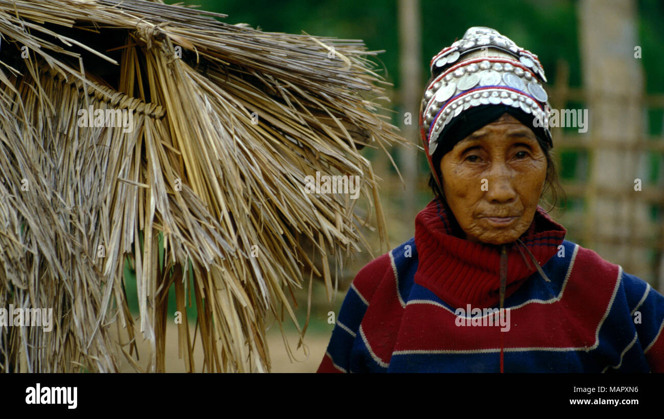 An indigenous Akha hilltribe woman in traditional silver headdress standing outside her straw hut in northern Thailand. - Stock Image