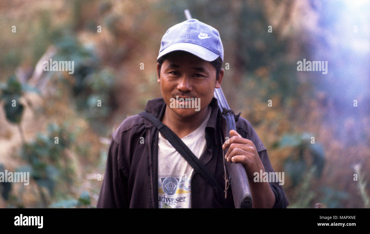 An indigenous Akha man is out hunting with his rifle in the forests of northen Thailand. - Stock Image