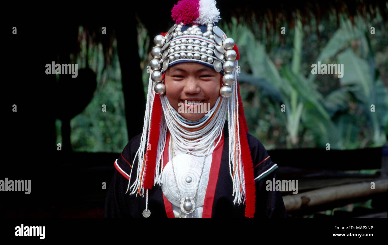 A young indigenous Akha hilltribe girl posing for a portrait in her people's traditional clothing in her village in northern Thailand. - Stock Image