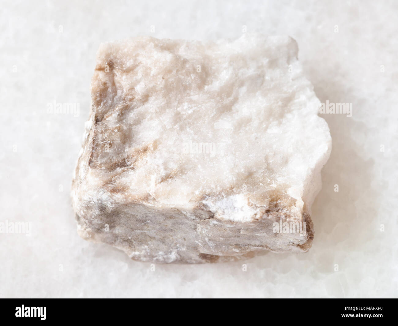 macro shooting of natural mineral rock specimen - rough Anhydrite stone on white marble background - Stock Image