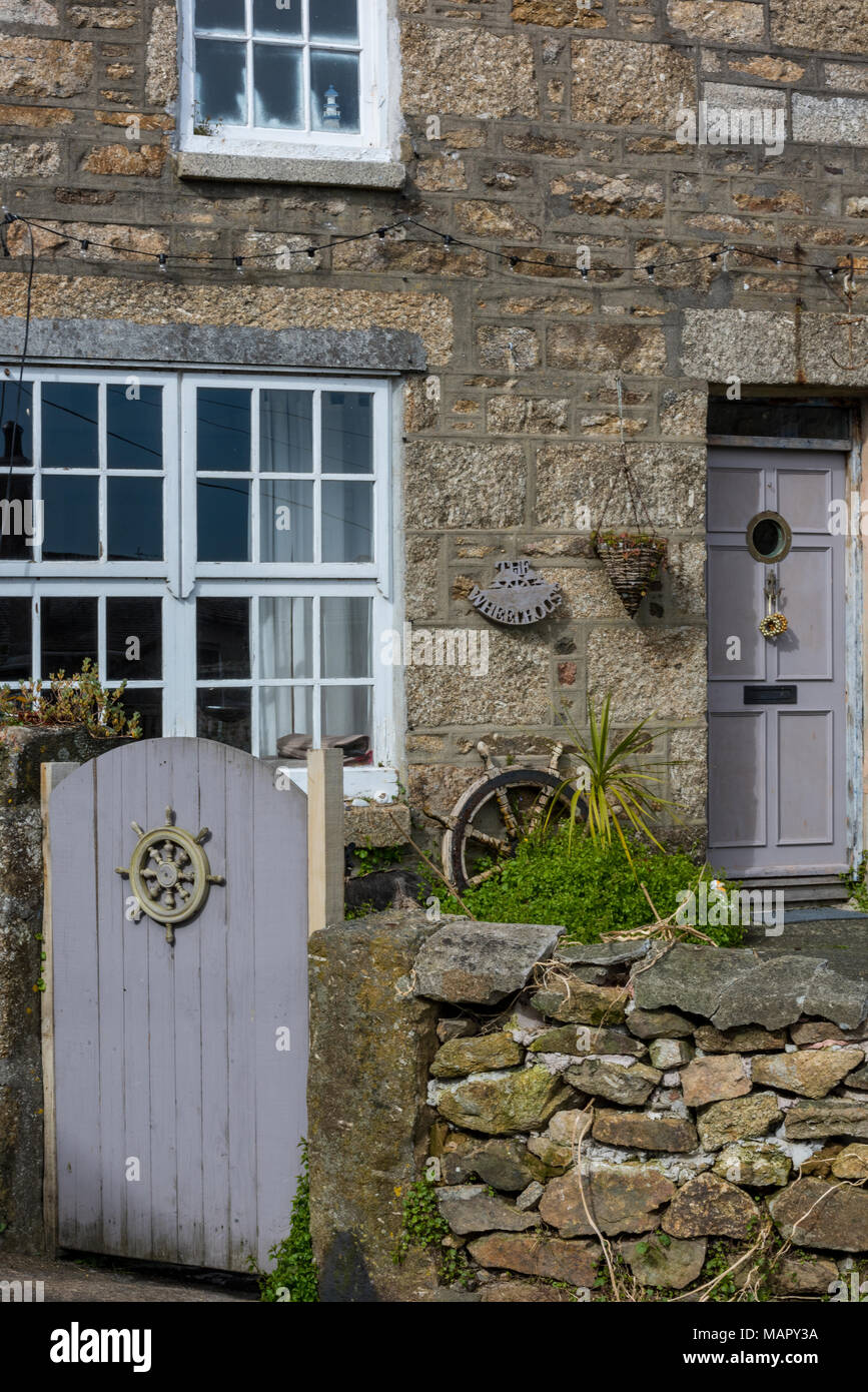 The front aspect of a typically Cornish old stone built cottage or house in a terrace in st Ives or saint Ives in cornwall with nautical decorations. Stock Photo