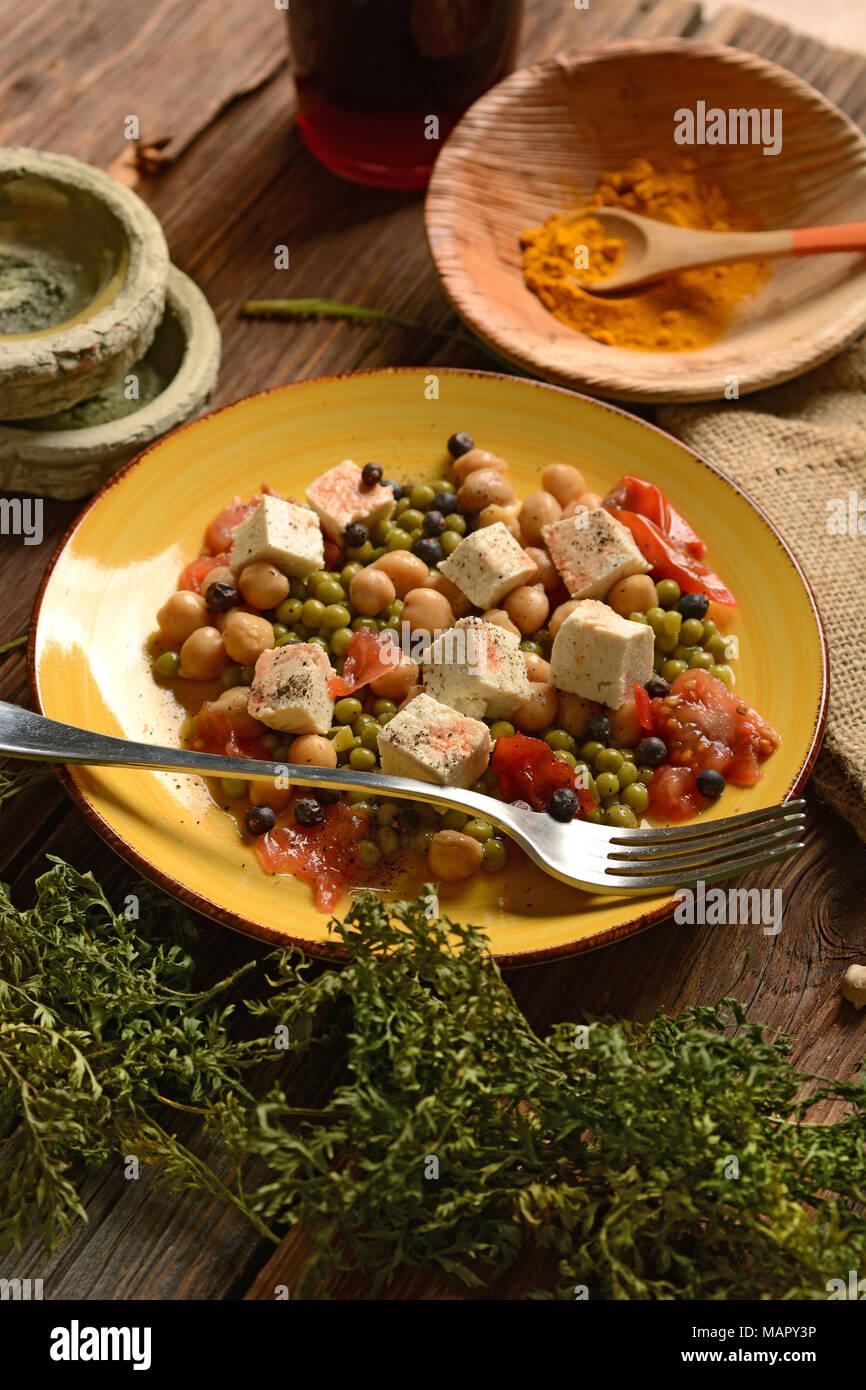 tofu salad, chickpeas, peas and tomato - vegetarian food - closeup Stock Photo