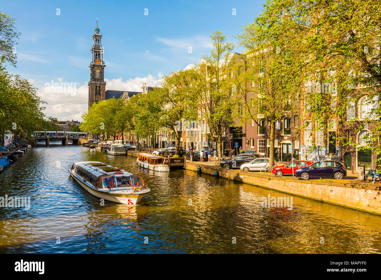 Boat on Prinsengracht Canal, with Westerkerk in the background, Amsterdam, Netherlands, Europe - Stock Image