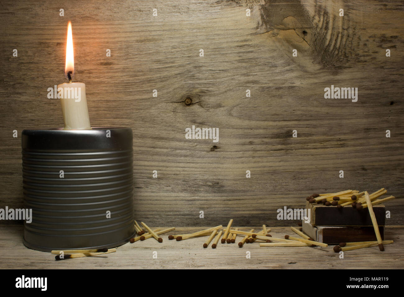 Matches and a burning candle on wooden background - Stock Image