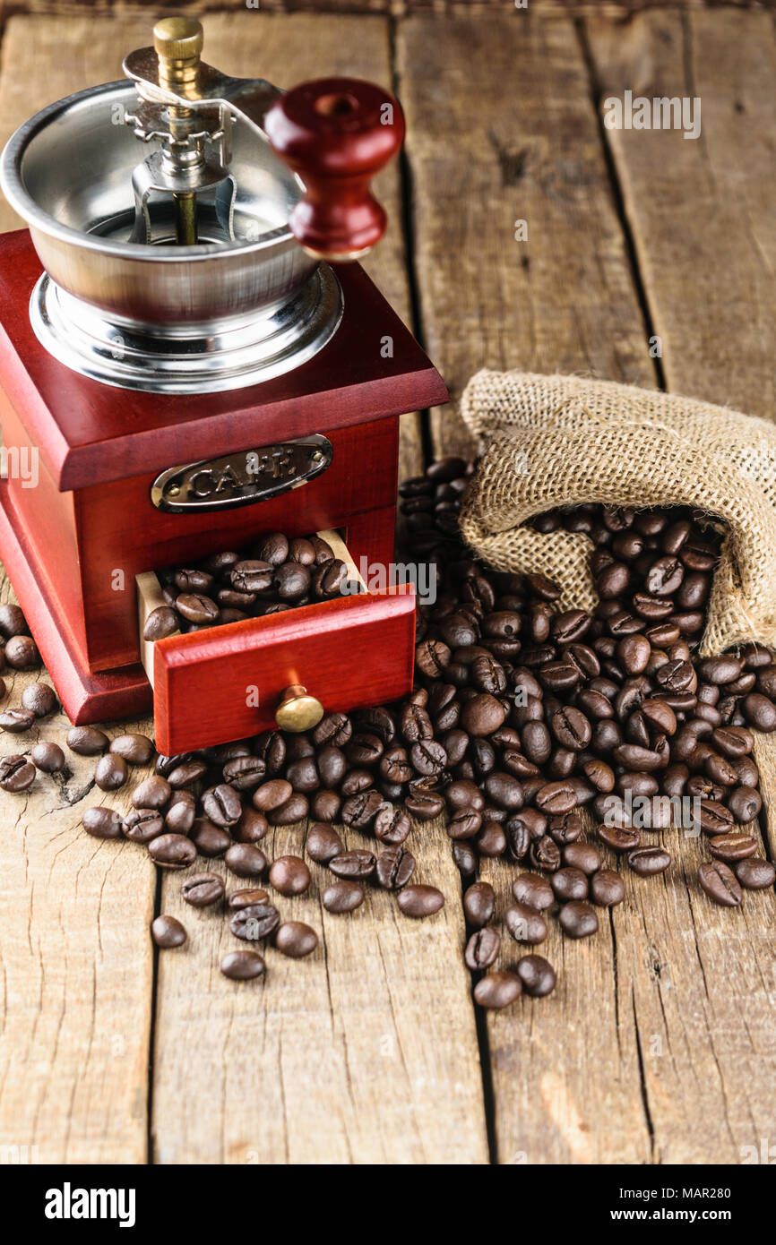 coffee beans in jute bag with coffee grinder on wood. - Stock Image