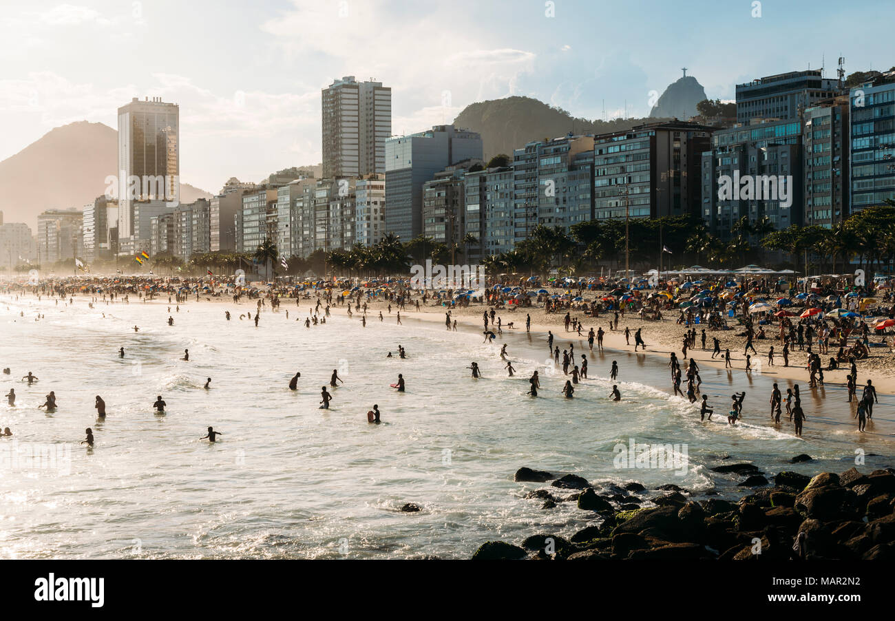 Crowded Copacabana Beach with distant view of Christ the Redeemer statue far right, Rio de Janeiro, Brazil, South America - Stock Image