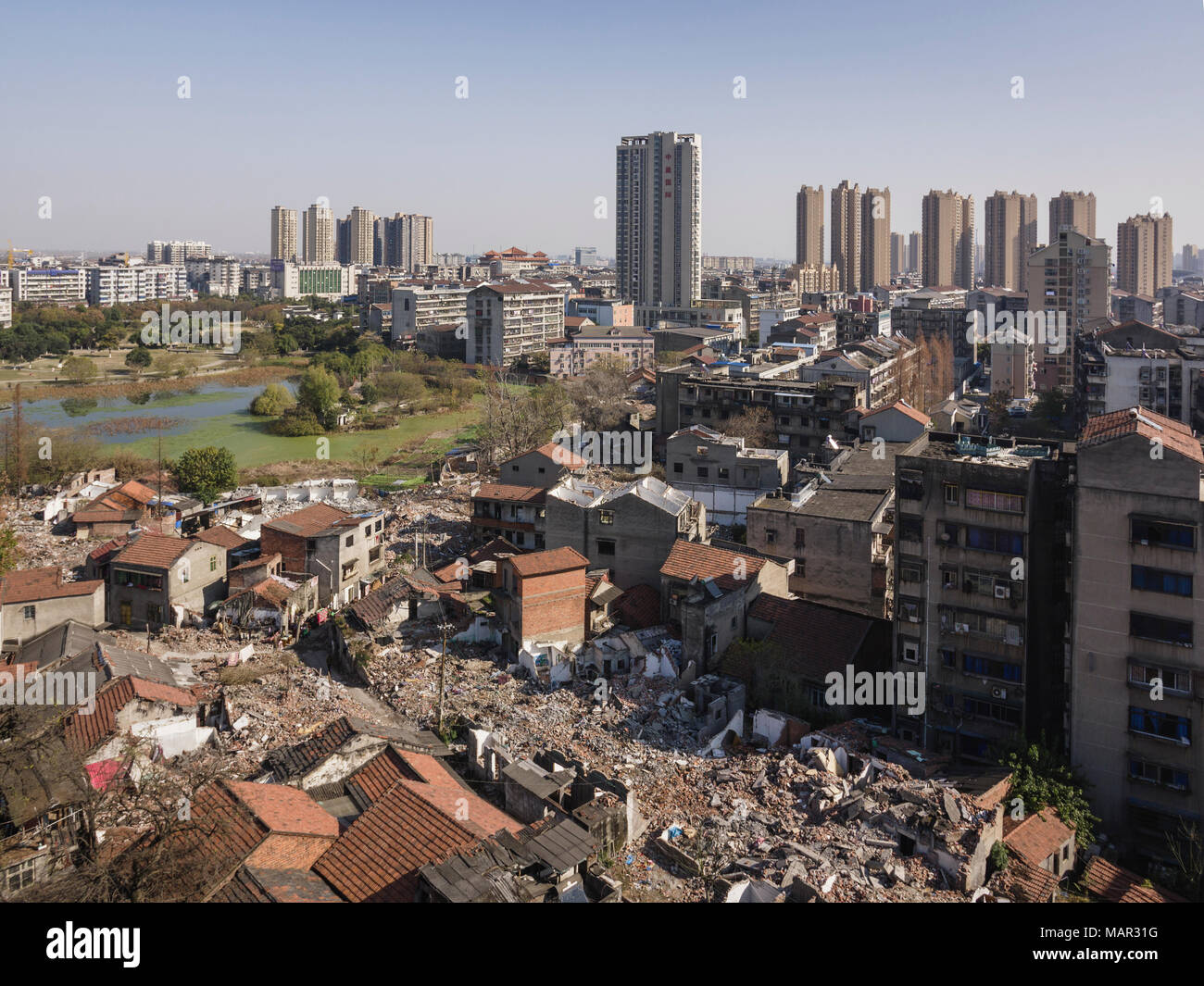 Tall buildings rise behind torn down old apartment buildings, Jingzhou, Hubei, China, Asia - Stock Image
