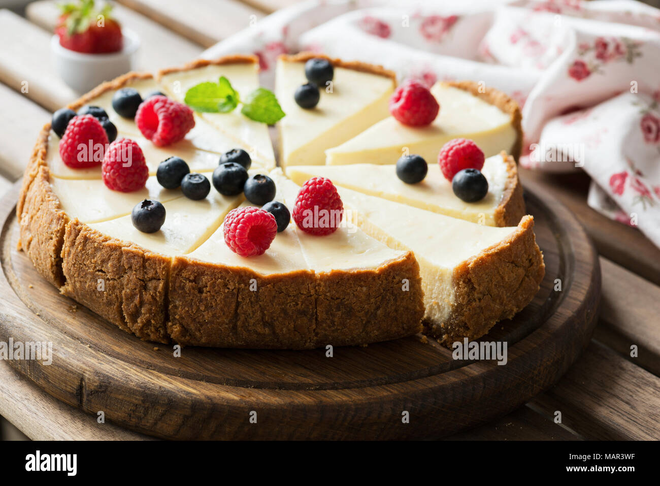 Classical Cheesecake with fresh berries on wooden board, selective focus, horizontal composition - Stock Image