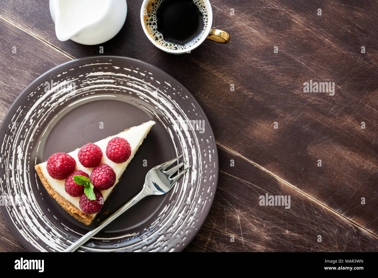Top view cheesecake with raspberries, cup of coffee and cream on wood. Copy space for text - Stock Image