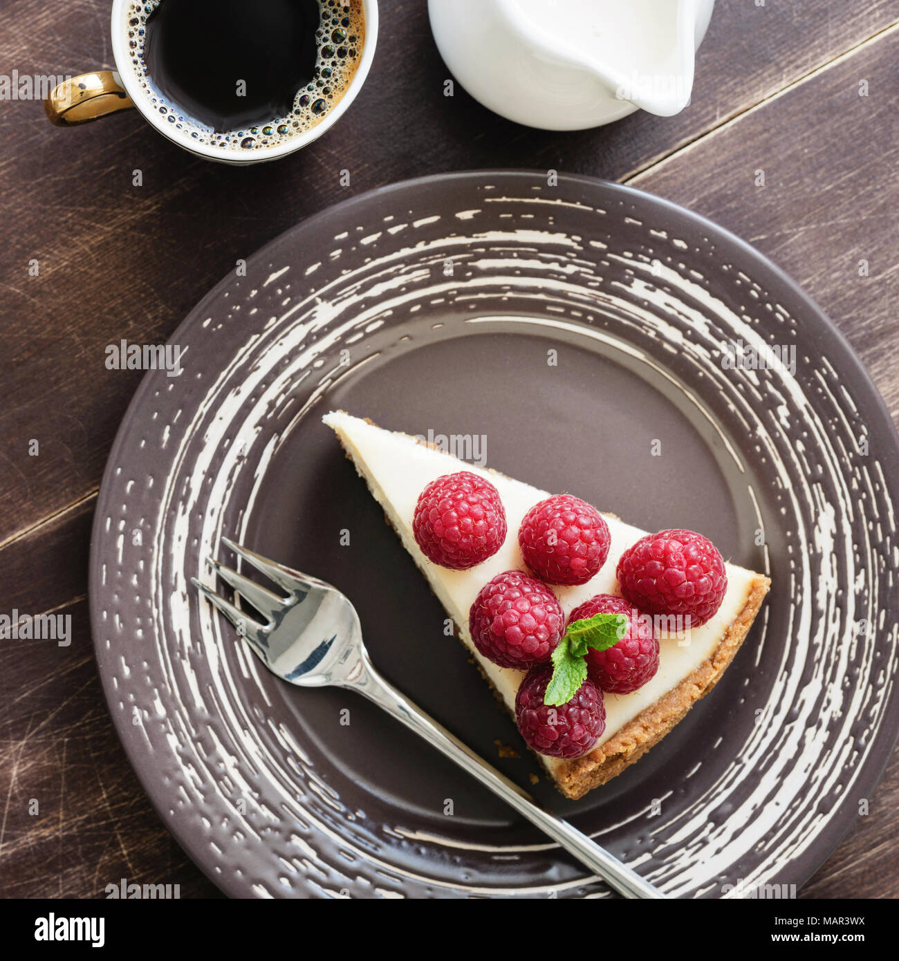 Cheesecake with raspberries, coffee and cream. Top view, square crop - Stock Image