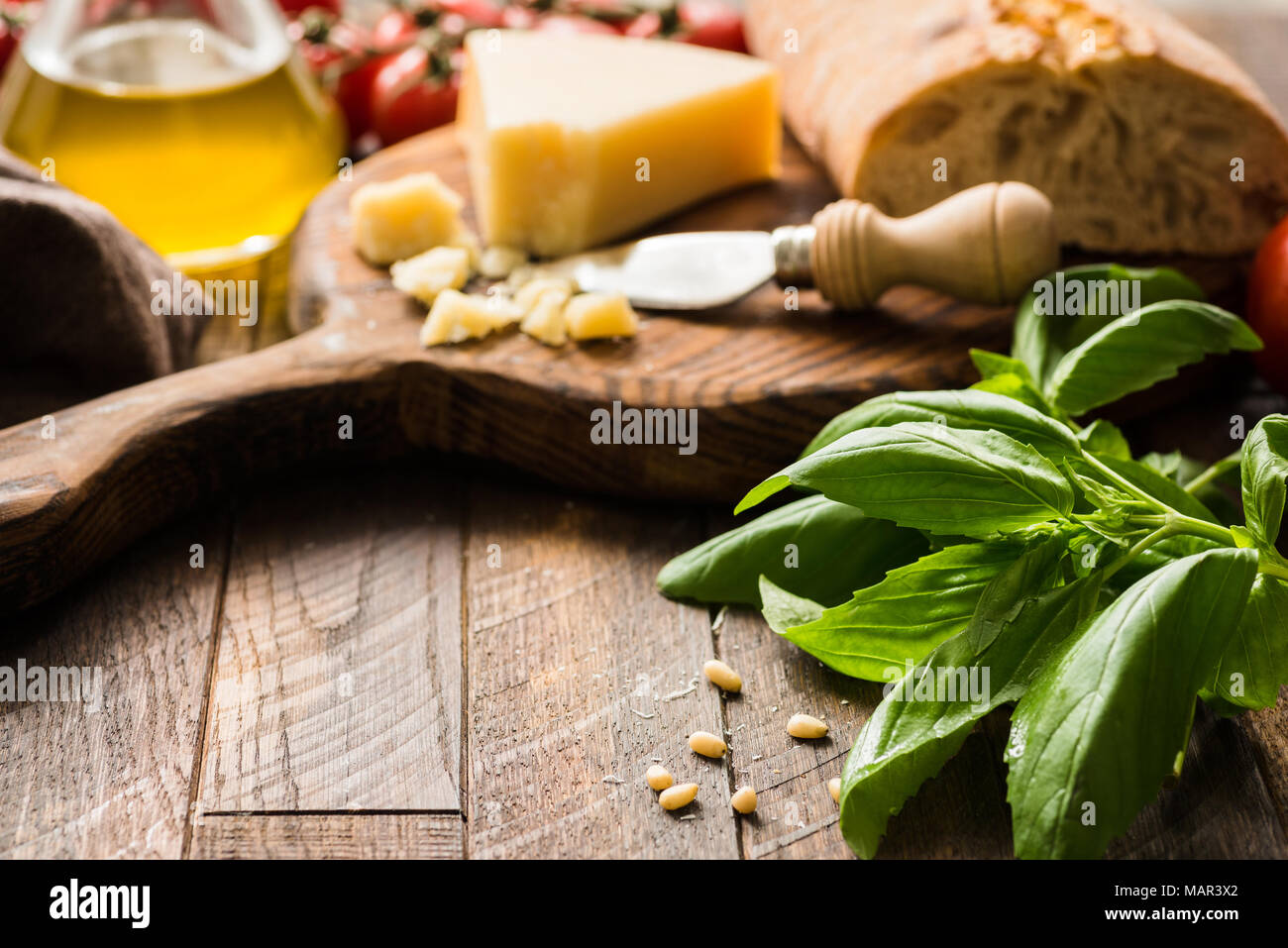 Italian food background with parmesan cheese, olive oil, ciabatta and basil leaves on rustic wood. Copy space for text, selective focus - Stock Image