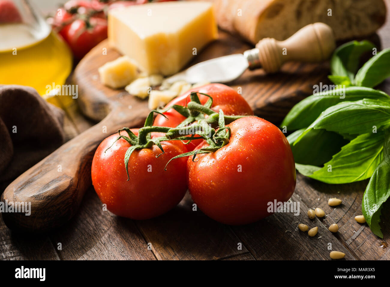 Tomatoes on vine, olive oil and parmesan cheese. Italian food background or still life - Stock Image