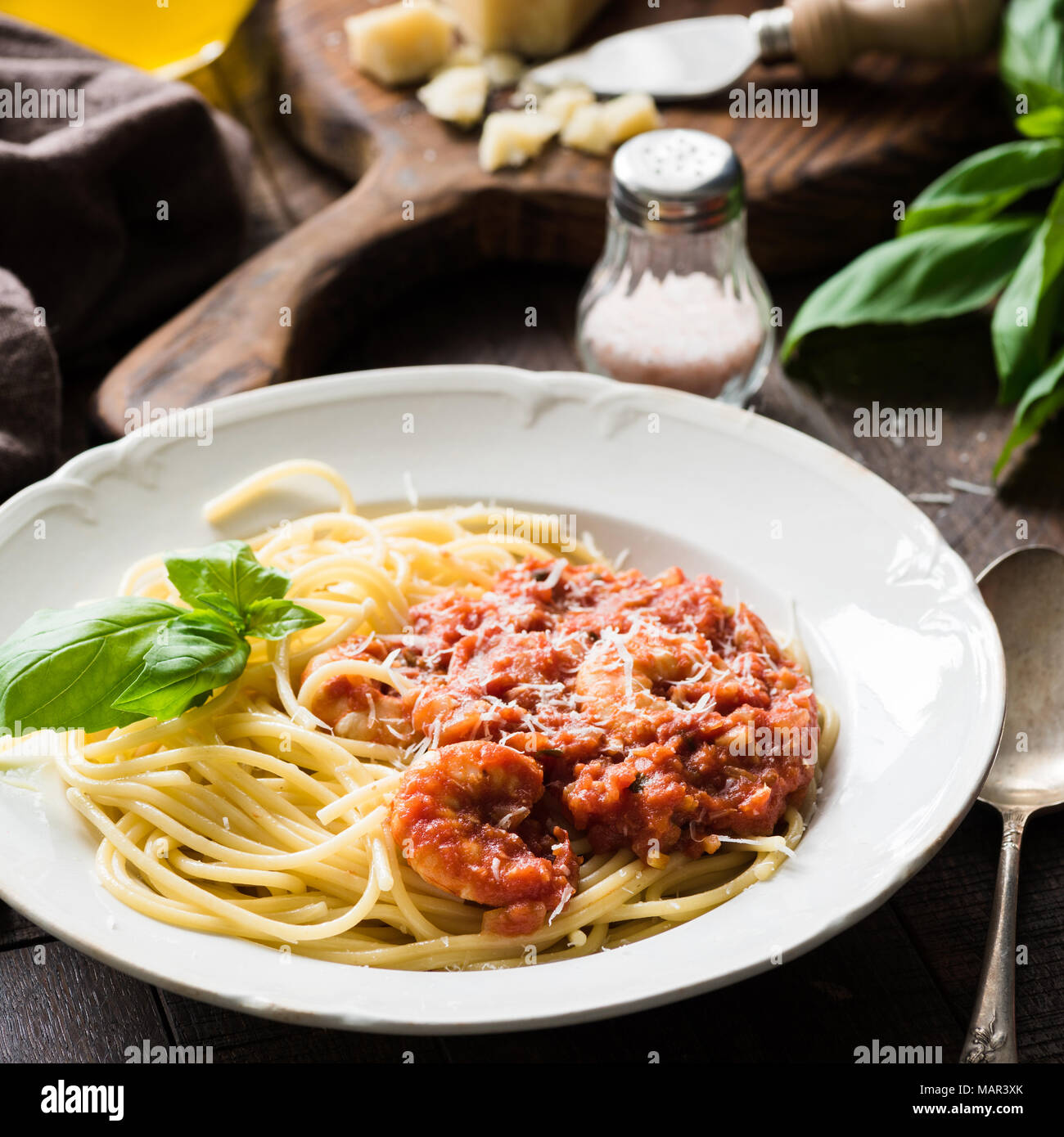 Italian pasta with tomato sauce and shrimps on white plate, cloeup view, square crop Stock Photo