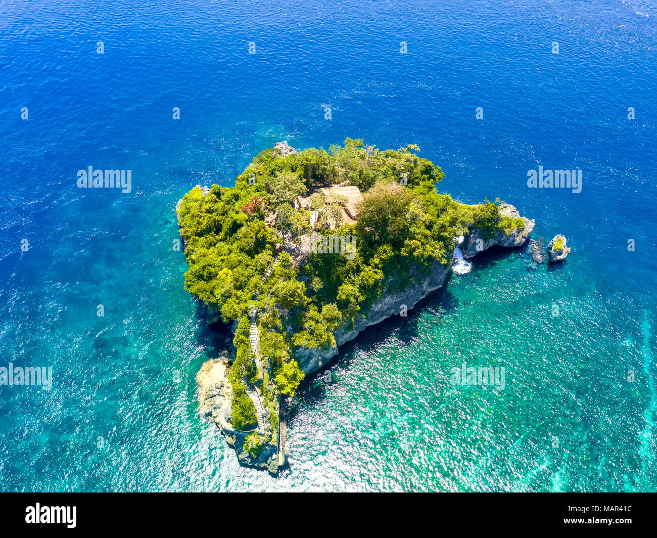 Indonesia. Emerald ocean water. A small rocky island, overgrown with jungles. Stairs from the water and a few huts between the trees. Aerial view - Stock Image